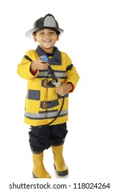 """An adorable preschool """"fire chief"""" in full gear.  He's happily aiming his hose.  On a white background."""
