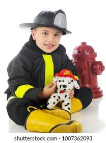 """An adorable preschool """"fireman"""" happily showing off his dalmation fire dog.  On a whtie background."""