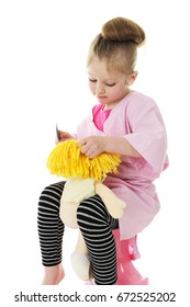 """An adorable preschool girl in her """"hairdresser"""" smock, combing her dolls blond yarn hair.  On a white background."""