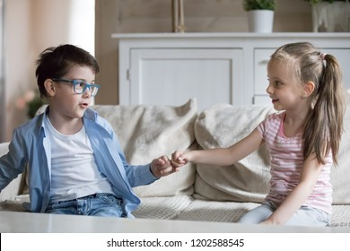 Adorable preschool kids sitting on sofa at home. Little children reconcile after fight or quarrelling making peace with hand gesture hold hands joining pinkies swear no more arguing be friends forever