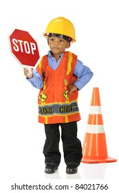 "An adorable preschool ""road crewman"" in a hardhat and safety vest, holding up a stop sign.  Isolated on white."