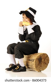 An adorable preschool-aged Pilgrim eating an ear of corn while sitting on an old log.