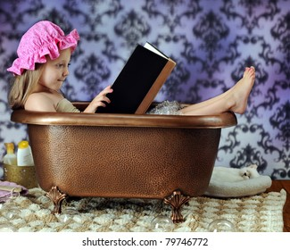An adorable preschooler in a bathing hat reading a book in a copper bathtub.