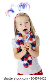 An adorable preschooler celebrating the Fourth of July with her accessories and licking a red, white and blue lollipop.  On a white background.