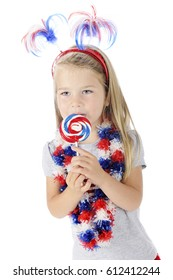 An adorable preschooler celebrating the Fourth of July with red, white and blue accessories, including the lollipop she's eating.  On a white background.