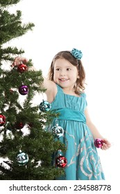 Adorable preschooler decorating the Christmas tree.  Isolated on white.