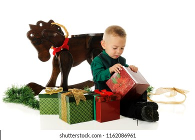 A adorable preschooler dressed up for Christmas, opening boxed gifts.  On a white background.