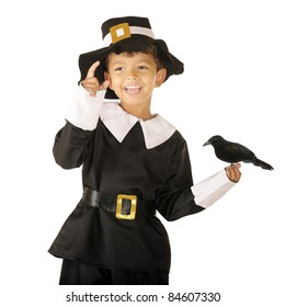 An adorable preschooler dressed as a pilgrim, laughing as a large crow is perched in his hand.  Isolated on white.  Some motion blur on his pointing hand.