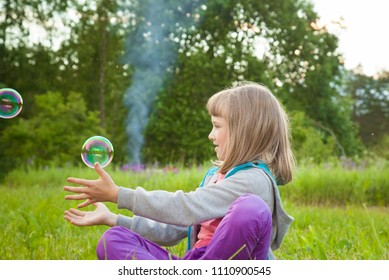 Adorable preschooler girl playing with soap bubbles sitting in a summer park