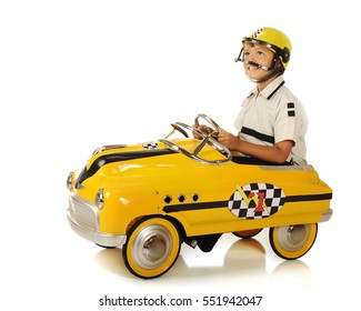 """An adorable preschooler in a helmet and pedal """"race car"""", looking up as he waits for a race to begin."""