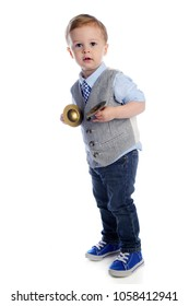 An adorable preschooler looking at the viewer as he stands, happily holding his toy cymbals. On a white background.