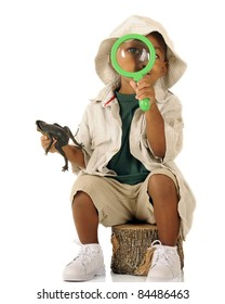An adorable preschooler looking at the viewer through a magnifying glass.  He's dressed in beige safari clothes and holds a frog in his other hand.