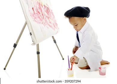 An adorable preschooler painting on an easel in his smock and  French beret.  On a white background.