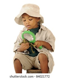 An adorable preschooler in a safari hat and explorer clothes examining a frog's belly with a magnifying glass.