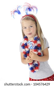 An adorable preschooler with U.S. colored accessories and enjoying a red, white and blue lollipop.  On a white background.