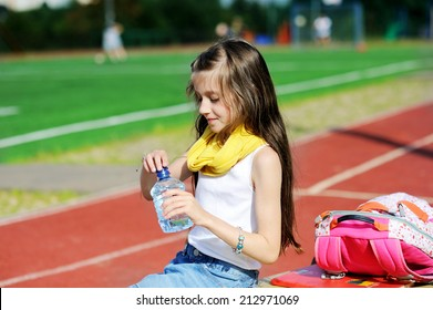 Adorable preteen girl in fashion outfit  drinking water at the school athletic field
