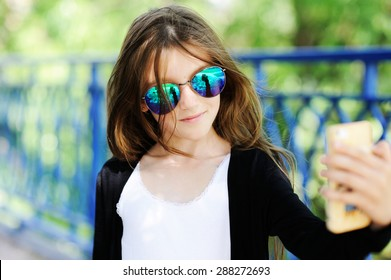 Adorable pre-teen tweenie kid girl in sunglasses making self portrait with funny  face on her  smartphone