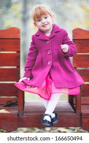 Adorable redhead little girl posing in pink coat , soft focus