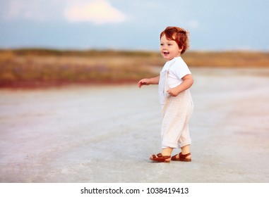 adorable redhead toddler baby boy in jumpsuit walking through the summer road and field
