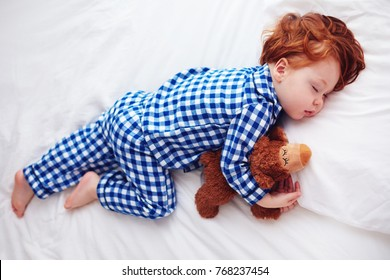 adorable redhead toddler baby sleeping with plush toy in flannel pajamas