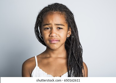 An Adorable sad african little girl on studio gray background