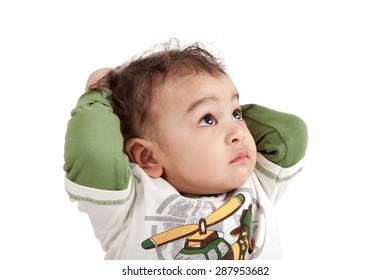 Adorable sad and curious indian baby boy looking upwards joining their hands on back head