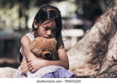 Adorable sad girl with teddy bear in park, Little girl is hugging a teddy bear.Upset child.