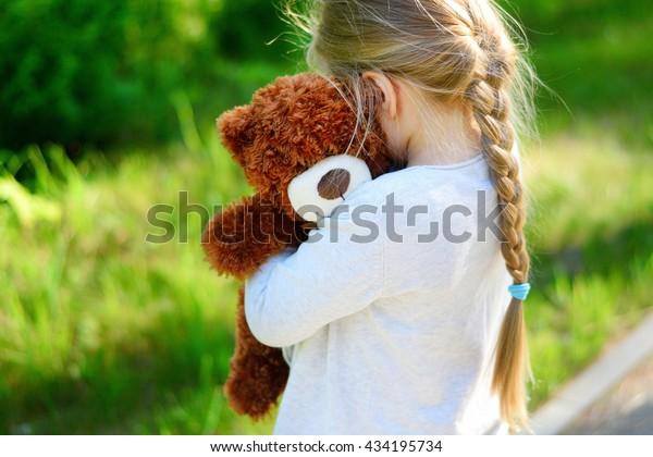 Adorable traurige Mädchen mit Teddybär im Park.