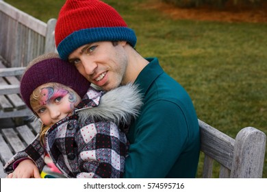 adorable school age girl daughter and mid 30s father hugging on bench during winter