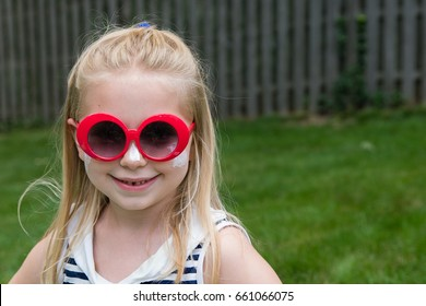 adorable school age girl in sunglasses with sunscreen on face and cheeks during summertime