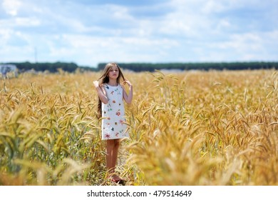 Adorable school aged kid girlwith long brunette hair having fun in the wheat firld on beauty summer day