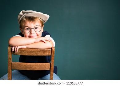 Adorable school boy with chalkboard copy space