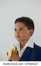 Adorable schoolboy eating banana against white background