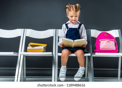 adorable schoolchild reading and sitting on chairs with books and backpack