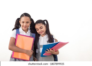 Adorable schoolgirls with uniform and notebooks on their hands. Best friends on school hugging on isolated white background with copy space for text.