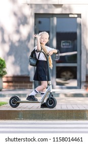 adorable schoolkid with backpack riding scooter, waving hand and looking at camera on street