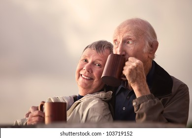 Adorable senior couple outdoors drinking from mugs