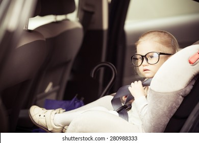Adorable serious little girl sitting in the car. Big funny glasses on her face. Toned image. Vintage style.