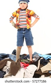 Adorable seven year old boy playing with pile of laundry.  Wearing mismatched clothes and underwear on his head.
