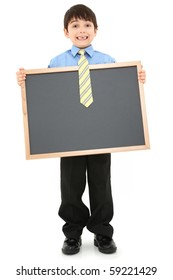 Adorable seven year old boy child in suit holding blank chalkboard over white background.