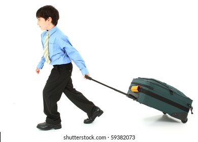 Adorable seven year old french american boy pulling large suit case over white background.