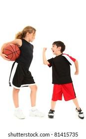 Adorable short boy child shaking fist at taller girl basketball player over white.