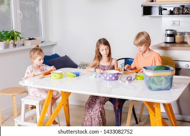 Adorable siblings cutting and preparing vegetables for the lunch,sitting at the kitchen table.Happy and healthy family life concept