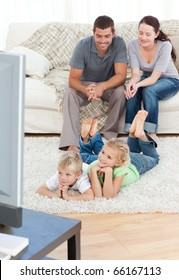 Adorable siblings watching television with their parents lying on the floor in the living-room