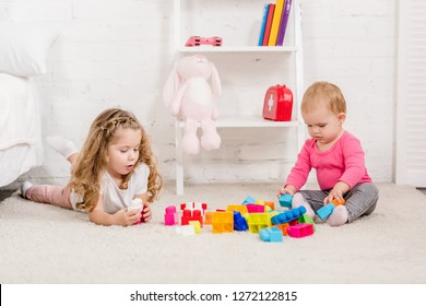 adorable sisters playing with constructor on carpet in children room