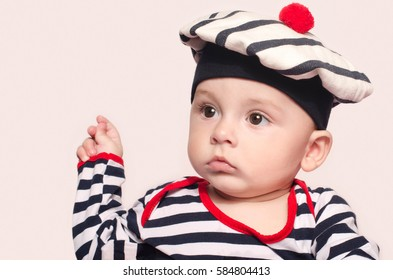 Adorable six month old child wearing a marine striped hat. Baby dressed nautical. Portrait of a cute baby boy looking to the side.