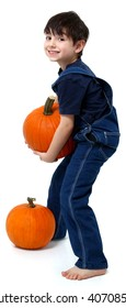 Adorable six year old boy in overalls with pumpkins over white.