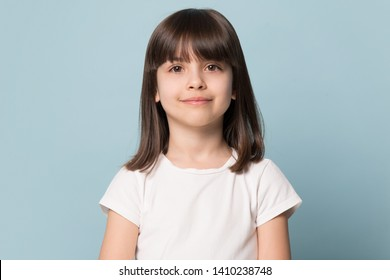 Photo of Adorable six years old girl in white t-shirt isolated on blue studio background, pretty brown-haired fringe hairstyle european appearance child pose indoor smiling look at camera, generation Z concept