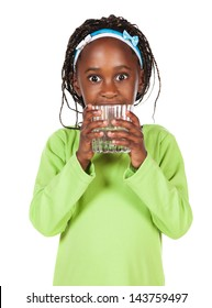 Adorable small african child with braids wearing a bright green shirt. The girl is holding a clear glass of water.