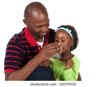 Adorable small african child with braids wearing a bright green shirt and blue jeans is with her father. He is wearing a red striped shirt and is helping her to drink water from a glass.